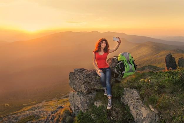 Randonneur femme prenant auto photo sur le sommet de la montagne