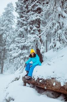 Randonneur femme profitant de la vue sur l'espace de copie de la forêt d'hiver enneigé