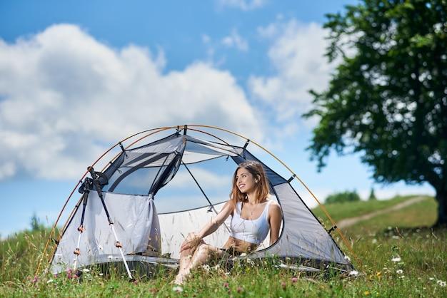 Randonneur fille assis à l'entrée de la tente au sommet d'une colline