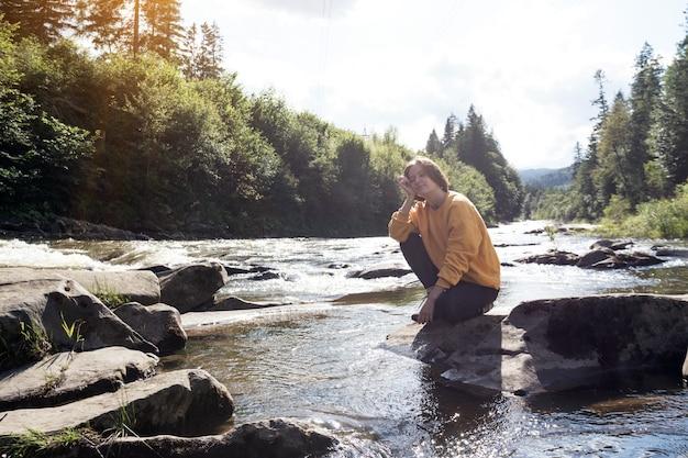 Randonneur de fille sur la banque d'une rivière de montagne