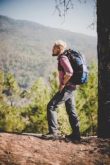 Randonneur avec un grand sac à dos voyageant vers la montagne.