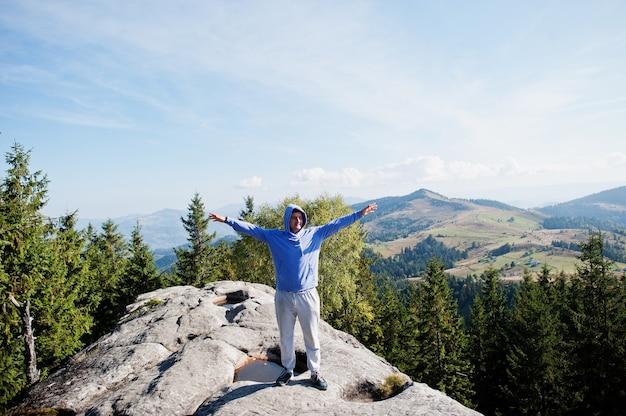 Randonneur heureux avec les mains en l'air debout sur le rocher. vue sur la vallée rocheuse.