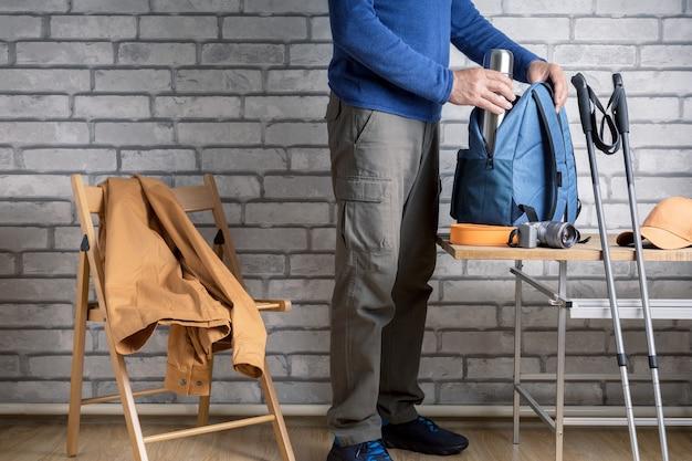 Randonneur homme debout avec des choses de randonnée disposées sur une table à la maison ou à l'hôtel. concept de voyage, d'aventure, de mode de vie actif.