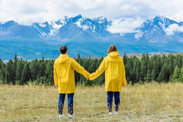 Randonneur homme et femme se tiennent la main et profiter de la vue sur les montagnes lors d'un voyage