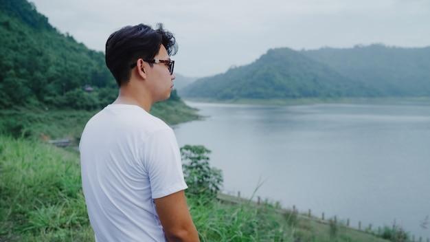Randonneur homme randonneur en randonnée aventure sentiment de liberté marchant dans la forêt près du lac en jour de pluie