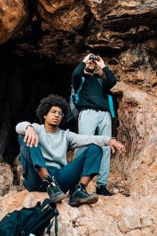 Randonneur homme regardant à travers les jumelles debout devant un jeune homme africain à l'entrée de la grotte
