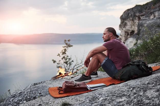 Randonneur homme réussi au sommet d'un rocher avec feu de camp. concept de liberté et de style de vie actif