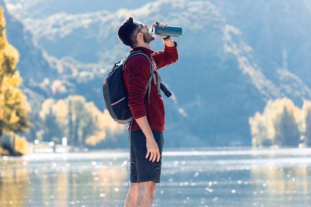 Randonneur jeune homme voyageur avec sac à dos de l'eau potable en se tenant devant le lac.
