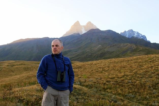 Randonneur avec des jumelles se dresse sur les montagnes. svaneti, géorgie