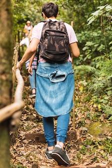 Randonneur marchant dans la jungle tenant un bâton