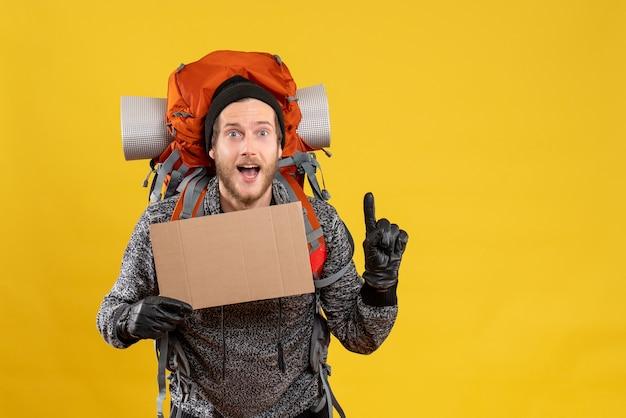 Randonneur masculin avec des gants en cuir et un sac à dos tenant un carton vierge surprenant avec une idée