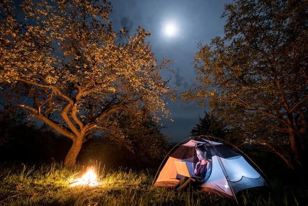 Randonneur près de feu de camp et tente touristique la nuit