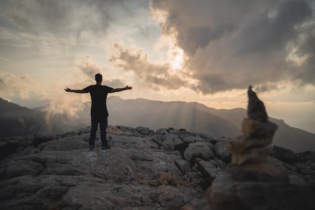 Randonneur profitant d'un magnifique coucher de soleil depuis le sommet d'une montagne