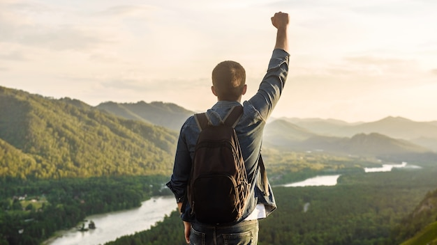 Randonneur avec un sac à dos au coucher du soleil au sommet d'une montagne