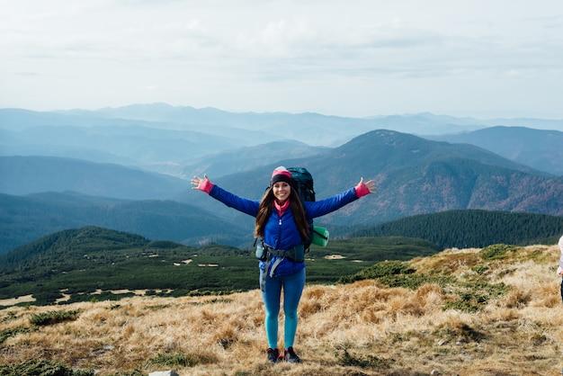 Randonneur avec sac à dos debout au sommet de la montagne avec les mains levées