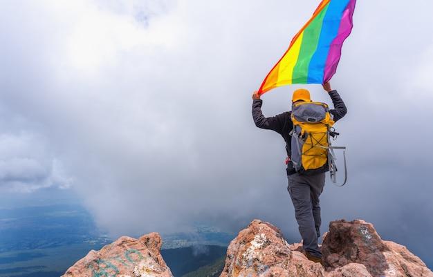 Un randonneur avec un sac à dos debout au sommet de la montagne et tenant un drapeau de la fierté