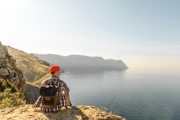 Un randonneur avec un sac à dos est assis au sommet de la montagne et profite de la belle vue sur la mer au coucher du soleil. concept de voyage et d'aventure. espace libre