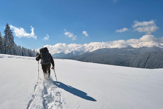 Randonneur avec sac à dos marchant sur une colline de montagne enneigée par une froide journée d'hiver.
