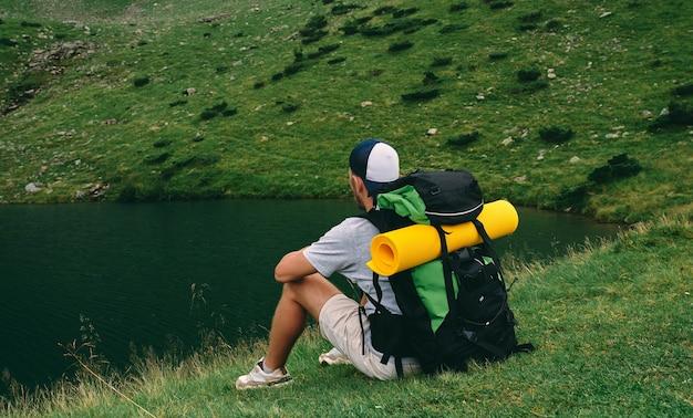 Un randonneur avec un sac à dos et un tapis en caoutchouc est assis sur l'herbe au bord du lac. jeune touriste au pied des montagnes verdoyantes. voyage, vacances, tourisme.