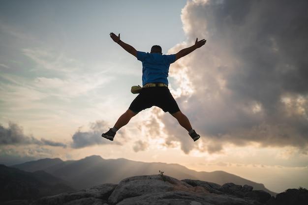 Le randonneur saute et profite d'un magnifique coucher de soleil depuis le sommet d'une montagne
