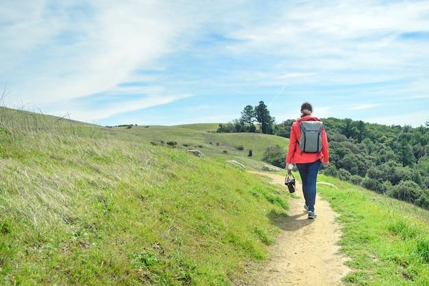 Randonneur en veste rouge avec sac à dos sur sentier dans un paysage magnifique
