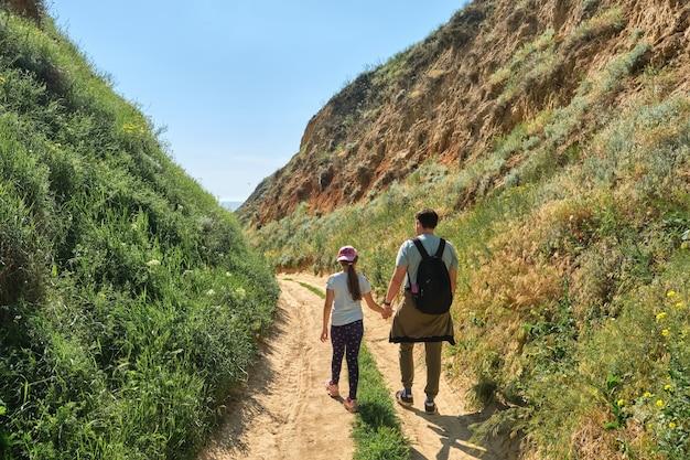 Randonneurs en famille marchant dans les collines verdoyantes. concept d'objectif, de réussite, de liberté et de voyage