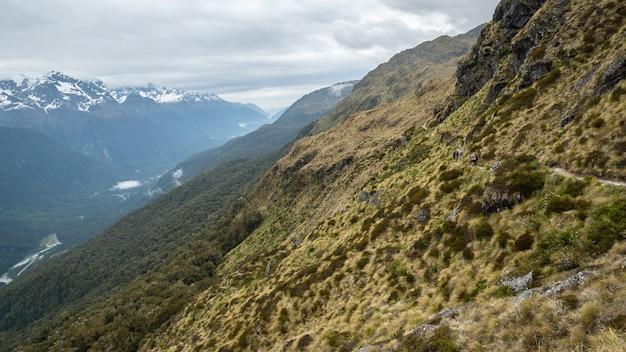 Randonneurs sur le flanc de la montagne avec vue sur la vallée alpine tourné sur routeburn track nouvelle-zélande