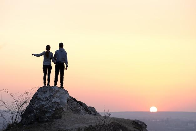 Randonneurs homme et femme debout sur une grosse pierre au coucher du soleil dans les montagnes. couple sur haut rocher dans la nature du soir. concept de tourisme, de voyage et de mode de vie sain.