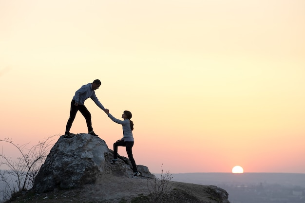 Randonneurs homme et femme s'entraident pour grimper la pierre au coucher du soleil dans les montagnes