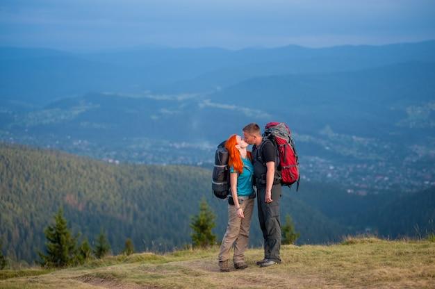 Randonneurs mec et femme aux cheveux roux s'embrassant sur la route en montagne