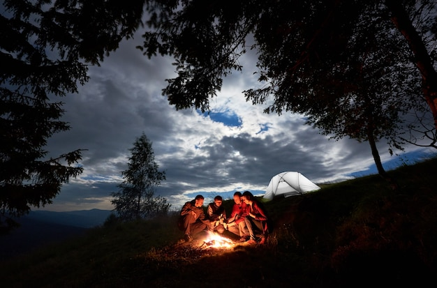 Randonneurs près d'un feu de camp et d'une tente en camping de nuit