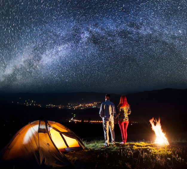 Randonneurs près de feu de joie et en appréciant le ciel étoilé