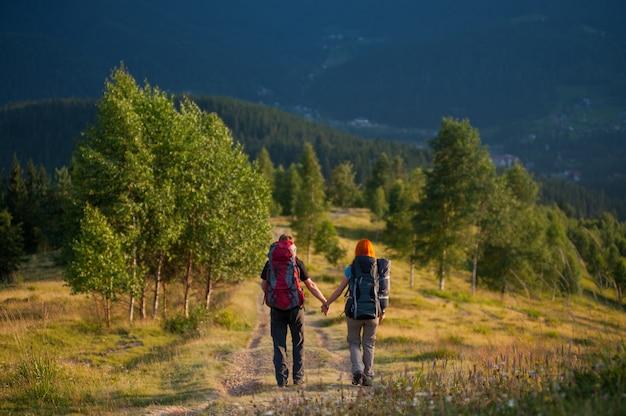 Randonneurs avec des sacs à dos marchant le long d'une belle région de montagne