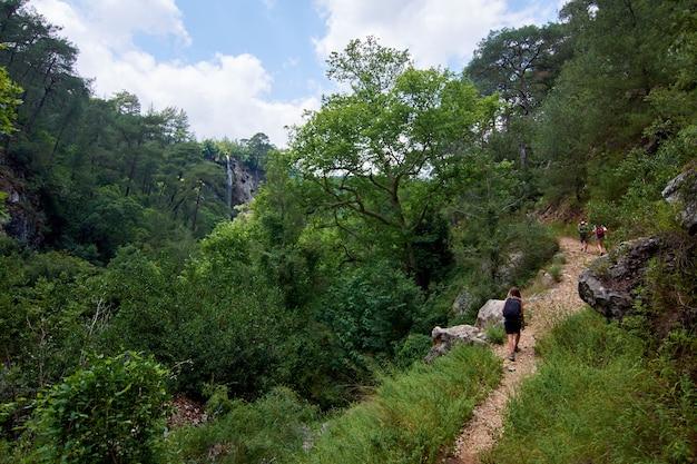 Les randonneurs avec des sacs à dos marchant sur un sentier étroit