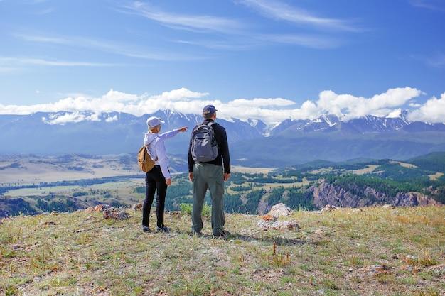 Randonneurs avec des sacs à dos se détendre au sommet d'une montagne. concept de style de vie voyage émotions heureuses. famille voyageant des vacances d'aventure actives