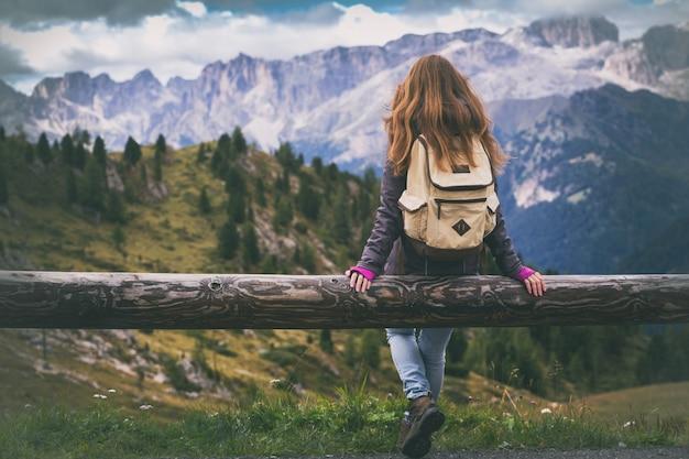 Randonneuse fille assise et regardant les montagnes enneigées. dolomites, italie.