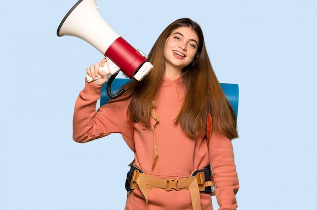 Randonneuse fille tenant un mégaphone sur bleu