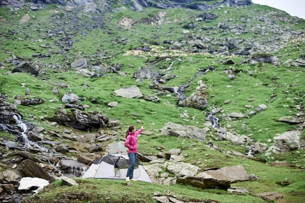 Randonneuse près de sa tente dans la vallée de la montagne