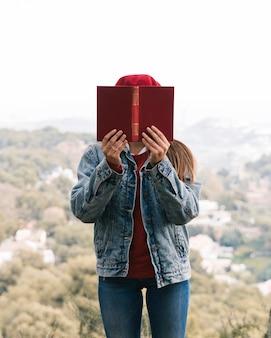 Une randonneuse tenant un livre rouge devant son visage, debout contre le fond flou
