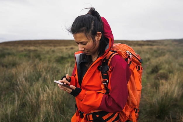 Randonneuse utilisant son téléphone dans un champ d'herbe
