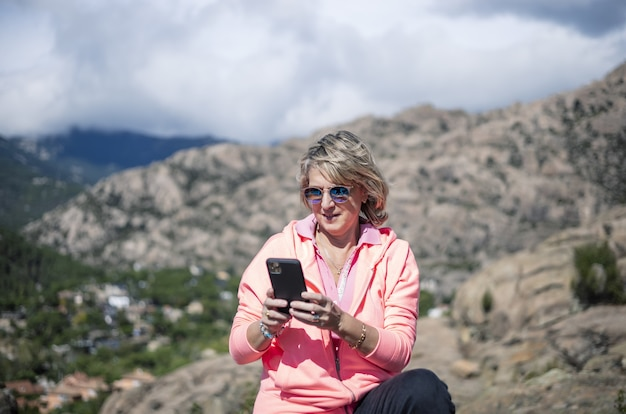 Randonneuse utilisant son téléphone et prenant des photos de la belle vue