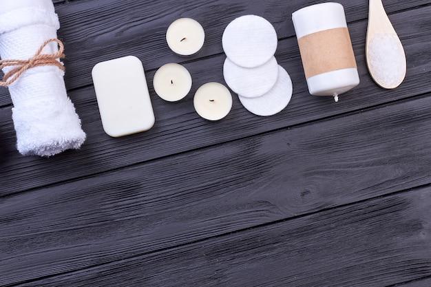 Rangée d'accessoires de traitement de spa blanc et espace de copie. fond de bois foncé rustique.