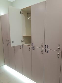 Une rangée d'armoires fermées numérotées dans le vestiaire des sports. l'un d'eux est ouvert et montre un cintre vide.