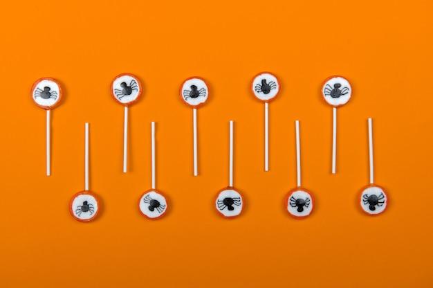 Rangée de bonbons d'halloween avec des araignées noires et une toile d'araignée sur fond orange, vue de dessus