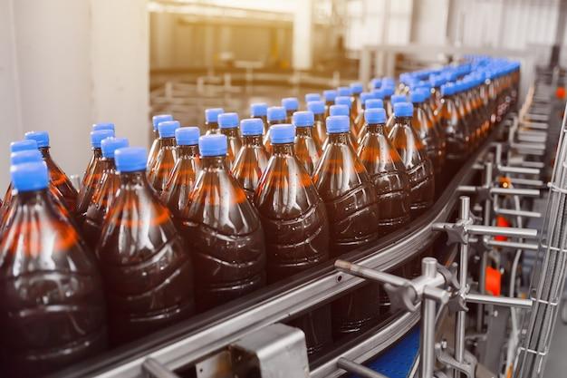 Rangée de bouteilles en plastique de bière brune sur la ligne de convoyeur de remplissage de bière