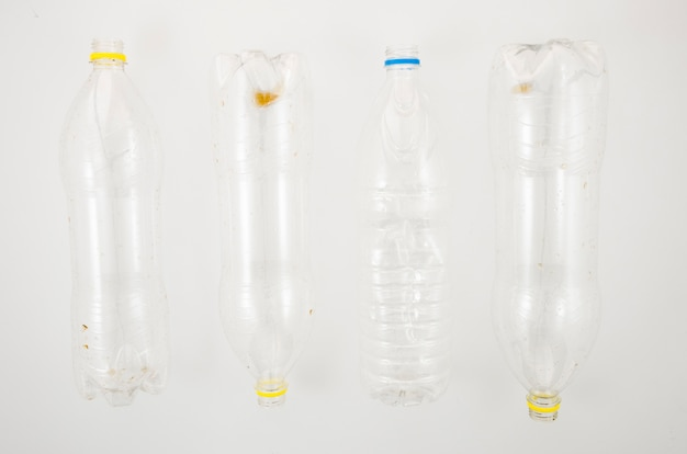 Rangée de bouteilles en plastique vides à recycler sur une surface blanche
