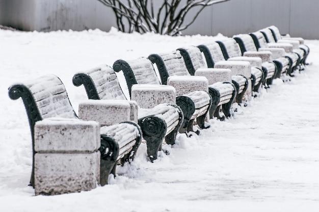 Rangée de boutiques blanches pour s'asseoir avec des urnes en hiver.