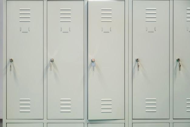Une rangée de casiers d'école en métal gris avec des clés dans les portes.