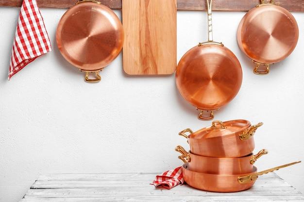 Rangée de casseroles en cuivre propres et brillantes de différentes tailles accrochées à une planche en bois
