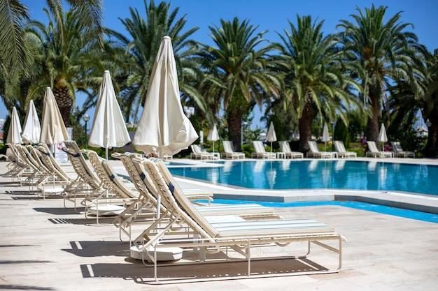 Rangée de chaises longues et parasols en plastique blanc près de la piscine avec de l'eau turquoise sur le fond des palmiers